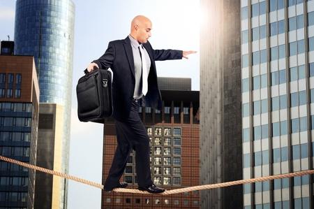 Businessman walking a rope in despair Stock Photo