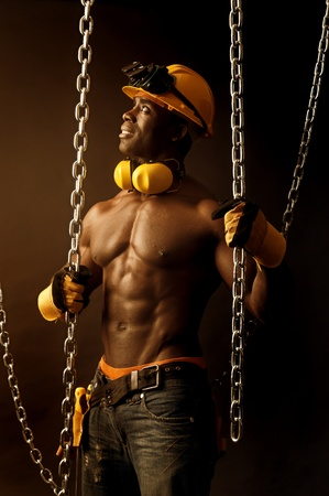 Strong build construction worker i a dark background with chains photo