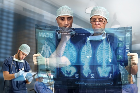 Doctors in a medical facility looking at digital screen photo