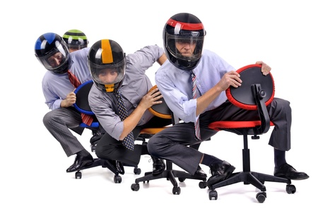 Businessmen racing in chairs with helmets