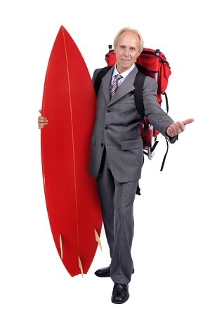 Mature businessman hitchhiking with backpack and surf board photo