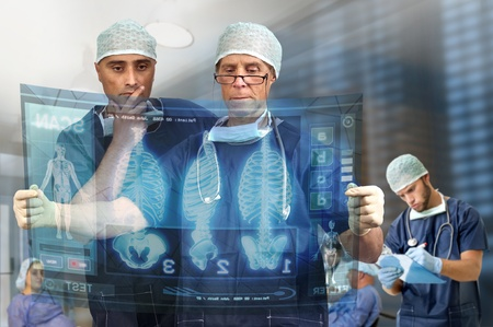 Doctors in a medical facility looking at digital screen