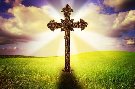 Beautiful image of a cross in a grass field with a holy cloudy sky photo