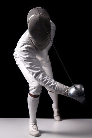 Male fencer isolated in a dark background Stock Photo