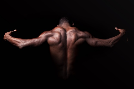 Beautiful and muscular black mans back in dark background Stock Photo