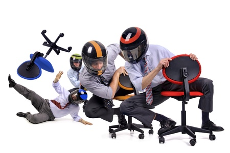 Businessmen racing in chairs with helmets photo