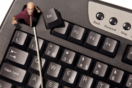 escape key: Businessman escaping from Escape key in a computer keyboard Stock Photo