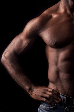 muscular arm: Beautiful and muscular black man in dark background
