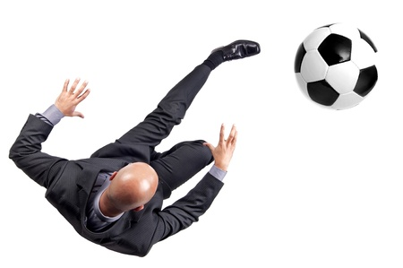 Businessman kicking a soccer ball isolated in white photo