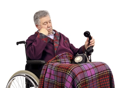 Lonely elderly in a wheelchairstaring at the phone photo