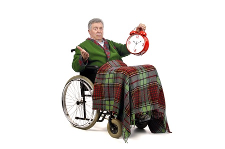 Lonely elderly in a wheelchair with big clock ticking    photo