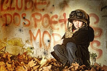 derechos humanos: Chico joven en una zona de guerra clama por ayuda