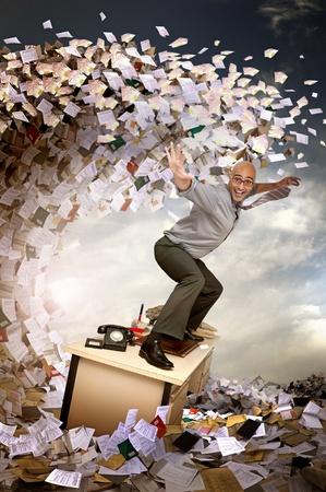 papeles oficina: Hombre de negocios navegar en un mar de papeles y archivos Foto de archivo