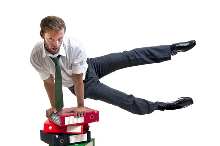 Businessman doing exercices over stack of files photo