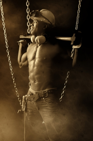 Strong build construction worker i a dark background with chains Stock Photo - 13611412