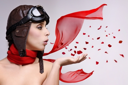 Beautiful girl with helmet and goggles blowing some rose petals photo
