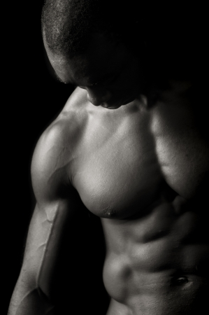 male chest: Beautiful and muscular black man in dark background