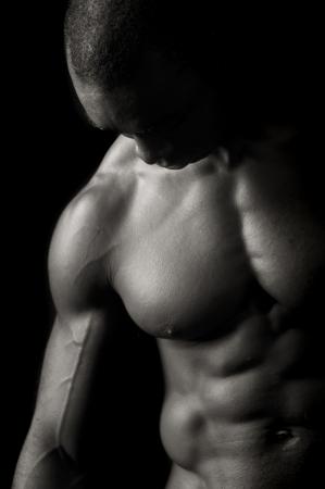 male model torso: Beautiful and muscular black man in dark background