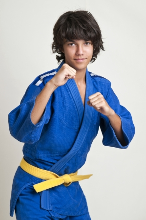 Young fighter posing against a light background photo