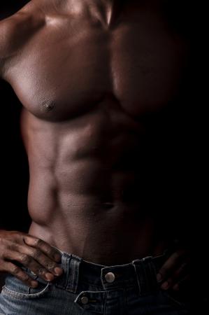 Beautiful and muscular black man in dark background photo