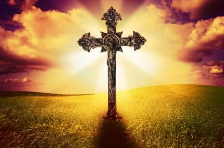 cruz de jesus: Bella imagen de una cruz en un campo de hierba santa con un cielo nublado