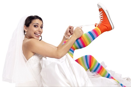 Funny bride with colorful socks putting orange shoes photo
