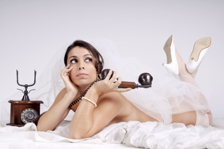 Beautiful bride in lingerie with phone photo