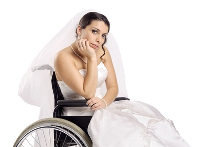 Beautiful disabled bride posing in a wheelchair photo