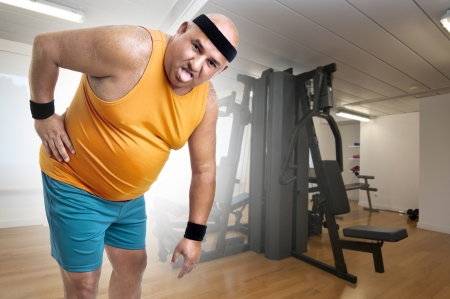 Large and tired fitness man with back pain  photo