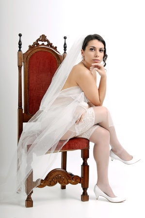 Beautiful bride seated in a chair in lingerie  photo