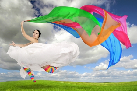 Happy bride jumping with coloful stockings and scarfs outdoors photo