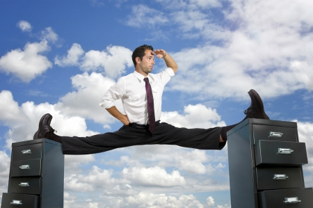 Businessman doing splits over cabinet files Stock Photo - 15469417