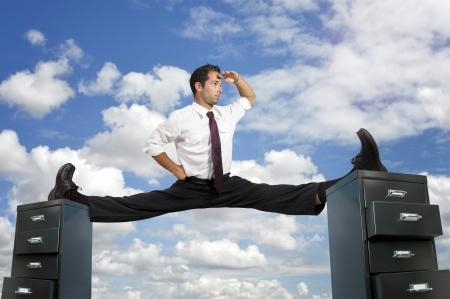 Businessman doing splits over cabinet files Stock Photo - 15469417