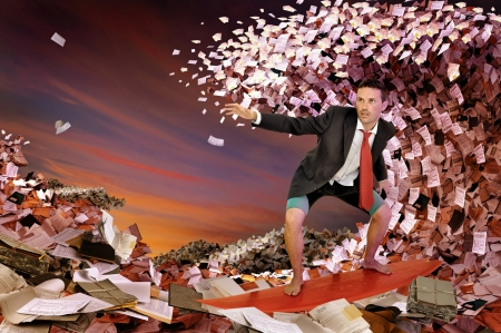 Businessman surfing in a sea made of files and papers Stock Photo