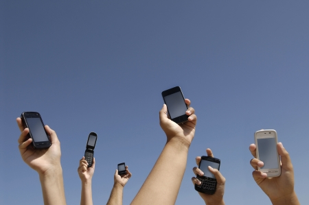 cell phones: Group of hands with different cellphones connecting