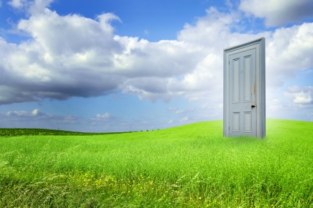 Isolated door in a grass field with blue cloudy sky photo