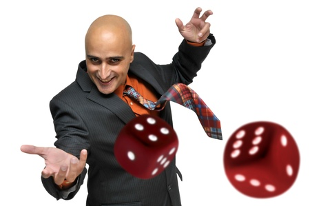 lucky man: Man in a suit playing dice isolated in white