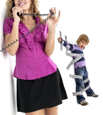 Junge an der Wand mit Klebeband gefesselt, so dass Mutter entspannen und haben ein Telefongespräch Standard-Bild