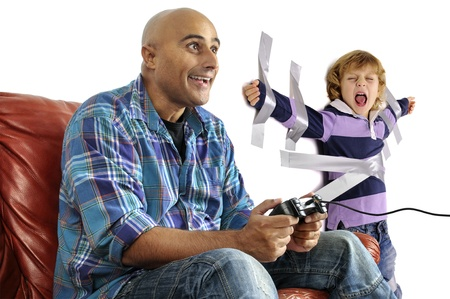 Young boy glued to the wall with duct tape, so daddy can play video games photo