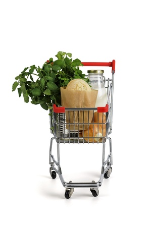 Shopping cart full with groceries isolated in white photo