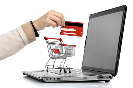 grocery cart: Laptop with small shopping cart and a hand with credit card isolated in white