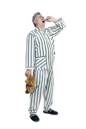 pijama: Hombre mayor en pijamas con el oso de peluche aislado en blanco