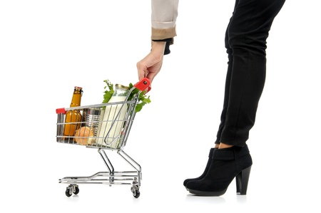 Woman pushing a small shopping cart full with groceries isolated in white Stock Photo - 16550401