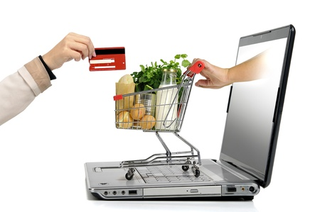 Hand with credit card and a small shopping cart coming from  laptop screen isolated in white photo