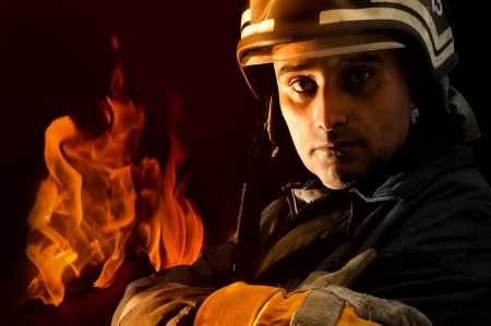 Portrait of a fireman with fire isolated in black Stock Photo