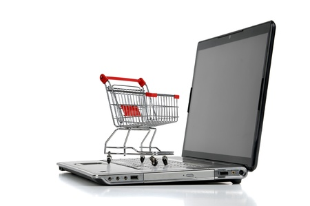 online shopping cart: Laptop with small shopping cart isolated in white Stock Photo