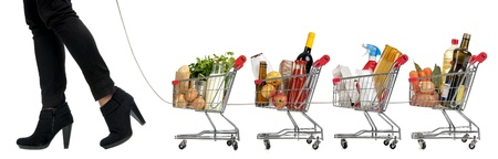 Woman pushing a convoy of small shopping carts full with groceries Stock Photo