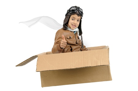 airman: Young boy pilot flying a cardboard box isolated in white