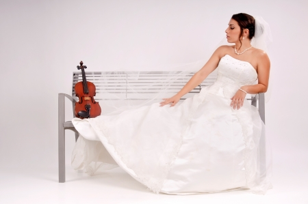 Beautiful bride posing in a park bench with a violin photo