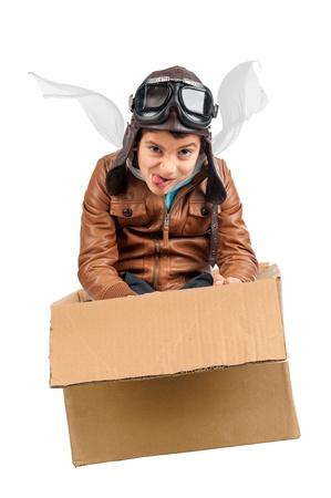 Ragazzo giovane pilota vola una scatola di cartone isolato in bianco Archivio Fotografico